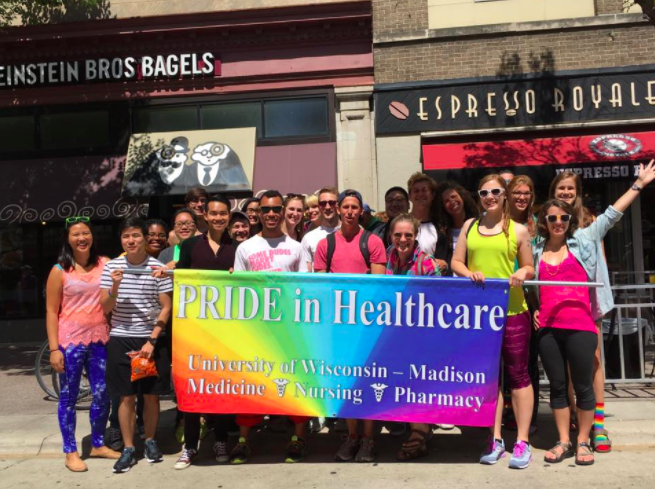 A big group of PRIDE in Healthcare members holding a big colorful banner