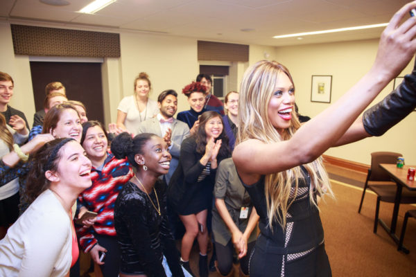 Laverne Cox taking a selfie with a crowd of students