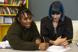 Two non-binary students doing work together in class.